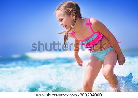 happy child girl on a  tropical beach ocean has a fun with splash - stock photo