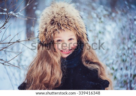 happy child girl on the winter walk in snowy forest,wearing fur hat