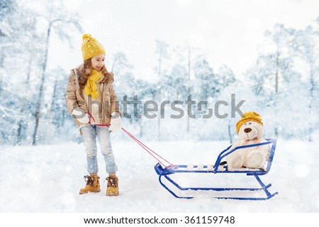 happy child girl plaing with a toy on a snowy winter walk. child rolls a teddy bear on a sled - stock photo