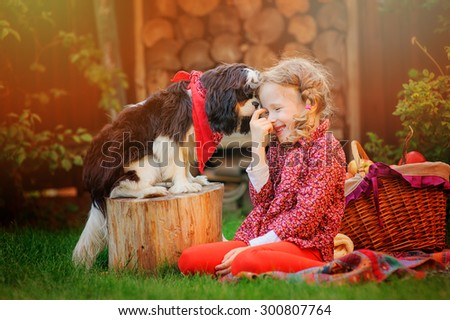 happy child girl playing and having fun with her cavalier king charles spaniel dog in autumn sunny garden - stock photo