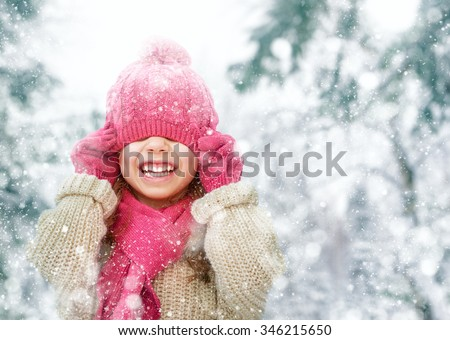 Happy child girl playing on a winter walk in nature - stock photo