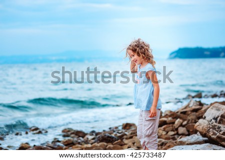 happy child girl playing on the beach, Traveling in Europe on summer vacations