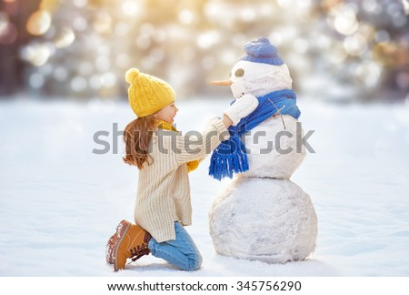 Happy child girl playing with a snowman on a winter walk in nature - stock photo