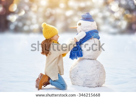 Happy child girl playing with a snowman on a winter walk in nature