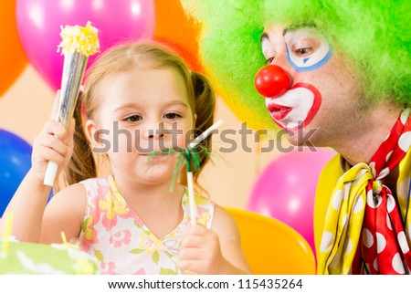 happy child girl playing with clown on birthday party - stock photo