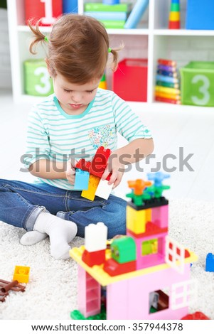 Happy child girl playing with toys and builds constructor