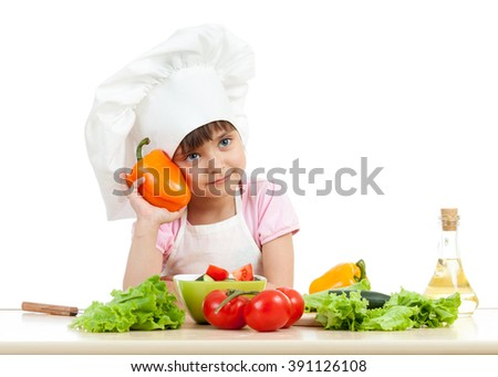 happy child girl preparing vegetarian dish