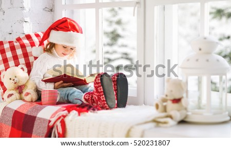 happy child girl reading a book while sitting at a winter window Christmas