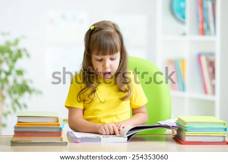 Happy child girl reading book at table in nursery