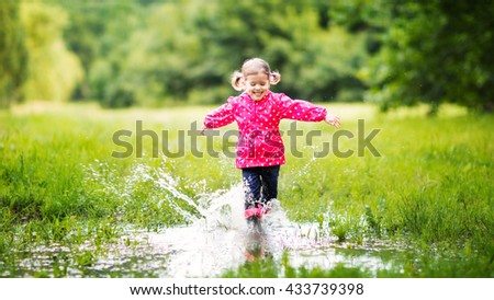 happy child girl running and jumping in puddles after rain in summer - stock photo