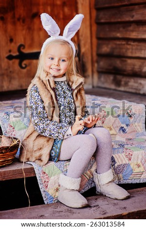 happy child girl wearing bunny ears for easter at country house - stock photo
