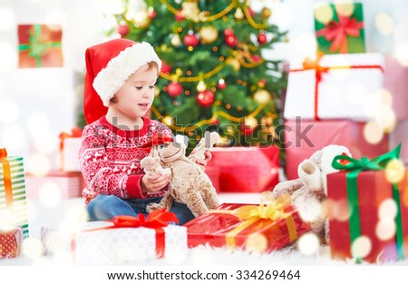happy child girl with Christmas gifts near a Christmas tree - stock photo