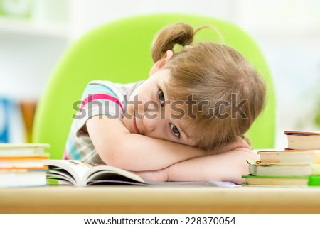 Happy child girl with stack books at table indoor - stock photo