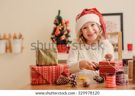 happy child girl wrapping christmas gifts at home, holiday indoor craft - stock photo