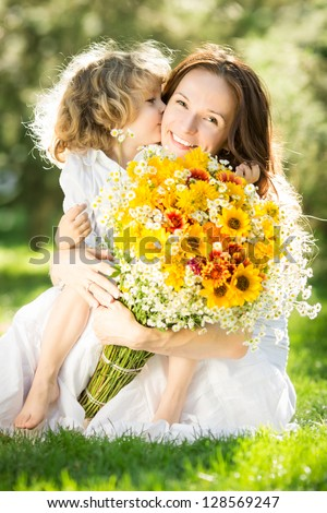 Happy child giving big bouquet of spring flowers to woman for mother`s day