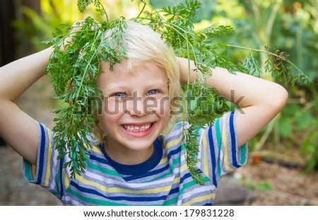 Happy child having playing fun in his vegetable garden, with carrot tops for hair - stock photo