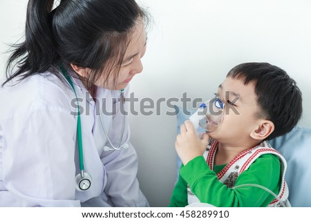 Happy child having respiratory illness helped by health professional with inhaler. Pediatrician take care asian boy with asthma problems making inhalation with mask on his face at hospital. - stock photo