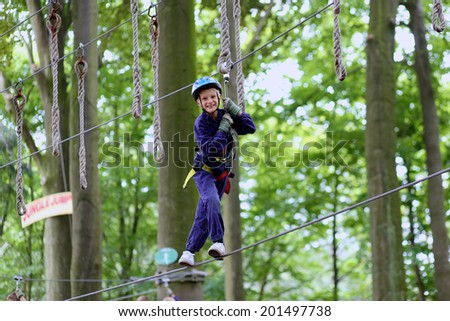 Happy child, healthy teenager school boy enjoying activity in a climbing adventure park on a summer day - stock photo