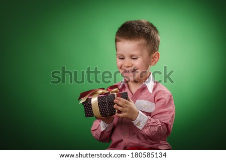 Happy child  holding a christmas present against green background  - stock photo