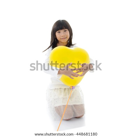 Happy child holding bunch of air balloon, yellow balloon heart shape - stock photo