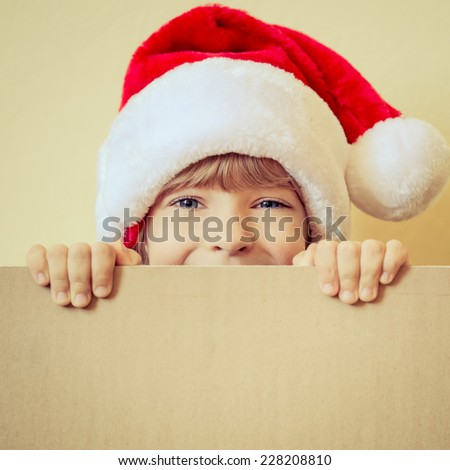 Happy child holding Christmas card blank. Kid dressed in Santa Claus hat playing at home. Xmas holiday concept. Copy space for your text - stock photo