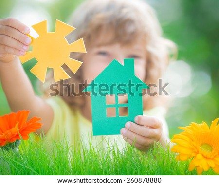 Happy child holding house and sun in hands against spring green background. Real estate business concept - stock photo