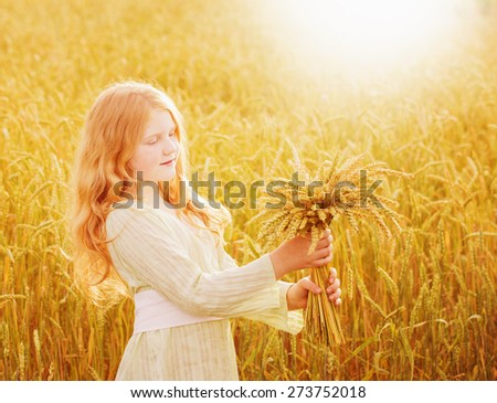 Happy child holding wheat ears at field - stock photo