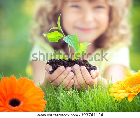 Happy child holding young plant in hands against spring green background. Ecology and Earth day concept - stock photo