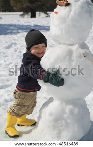 happy child hugs a snowman - stock photo