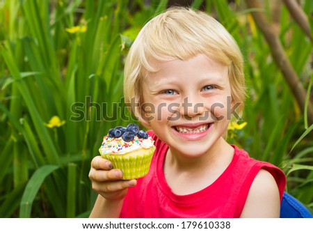 Happy child in a garden eating a colorful homemade cupcake  - stock photo