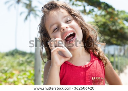 Happy child in a red shirt laughing at mobile phone outside - stock photo