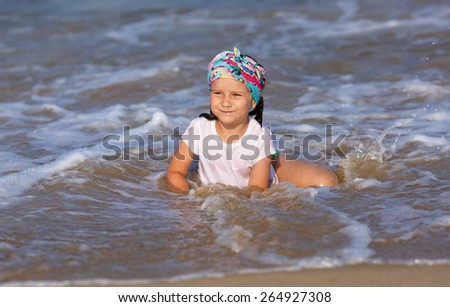 Happy child in a white t-shirt and colorful bandana having fun in the water at the beach. - stock photo