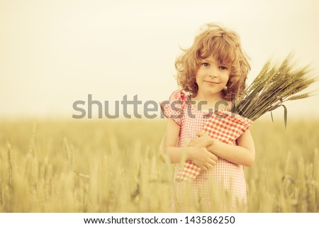 Happy child in autumn wheat field - stock photo