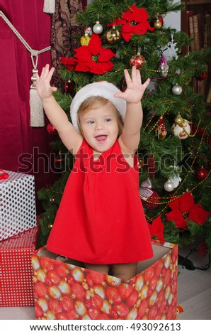 Happy child in costume of Santa in box with gifts