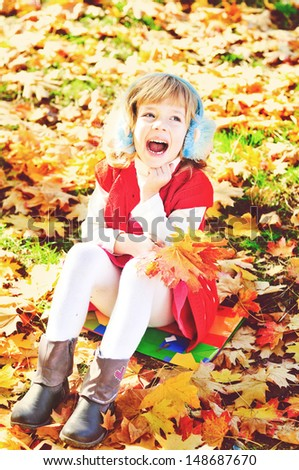 happy child in fall park sitting on the leaves - stock photo