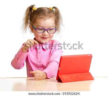 happy child in glasses looking at mini tablet pc screen sitting at table - stock photo