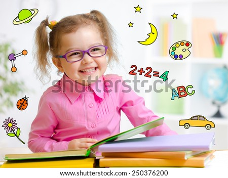 Happy child in glasses reading book. Early education in kindergarten concept. - stock photo