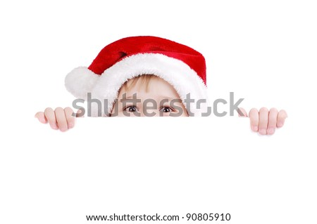 Happy child in Santa hat hiding face behind the blank board