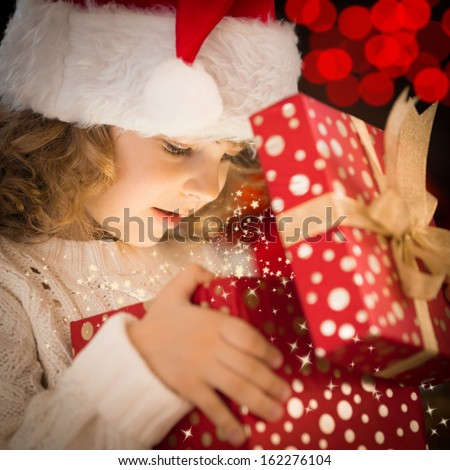 Happy child in Santa hat opening Christmas gift box - stock photo