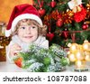 Happy child in Santa`s hat against decorated Christmas tree - stock photo