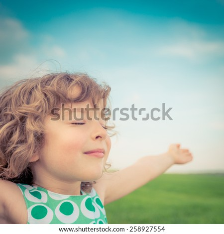 Happy child in spring field. Young girl relax outdoors. Freedom concept - stock photo