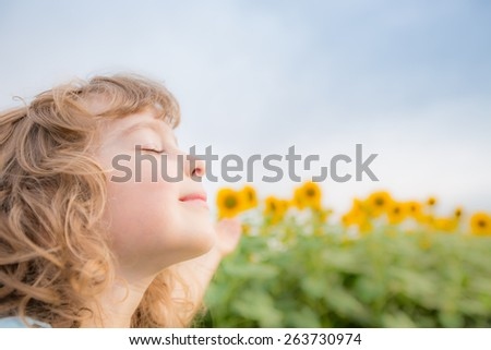 Happy child in spring sunflower field. Freedom concept - stock photo