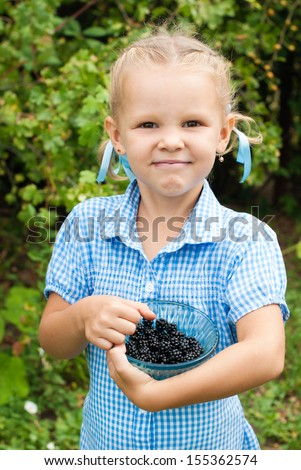 Happy Child in Summer.  Beautiful Girl with Blackberry in the Garden. Happy Children. Healthy Kids. Spring Time. Vacation in the Countryside.  Healthy Nutrition. - stock photo