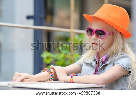 Happy child in sunglasses and orange hat. Pretty girl reading menu in cafe. Adorable toddler girl enjoying lunch at a beautiful outside cafe choosing meal from menu card - stock photo