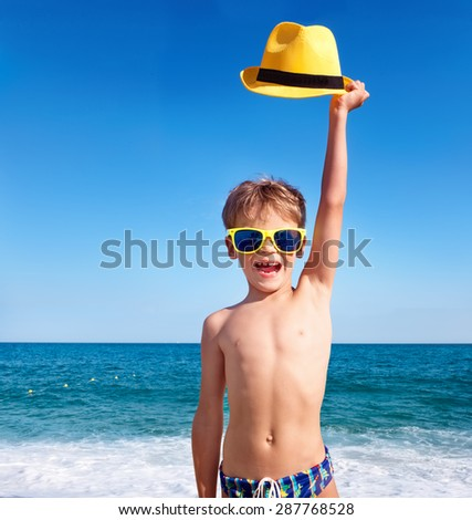 Happy child in sunglasses with yellow hat against sky background - stock photo