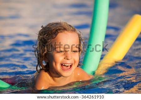 happy child in the pool, learning to swim with swimming noodle; warm sunset light - stock photo