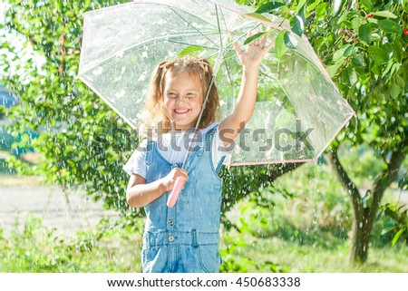 Happy child in the summer sunny rain. Funny little girl playing outdoors hot day with umbrella. Joyful emotions