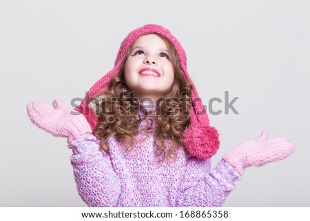 Happy child in winter hat and gloves in woolen sweater. Cute little girl in winter clothes and woolen accessories. Happy kid winter fashion. Studio, isolated, white background.  - stock photo