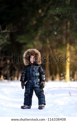 Happy child is in a winter forest. Sunny day and a lot of snow.