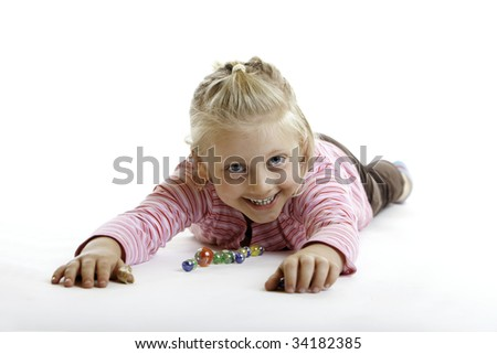 Happy Child is lying on the floor with marbles on white background